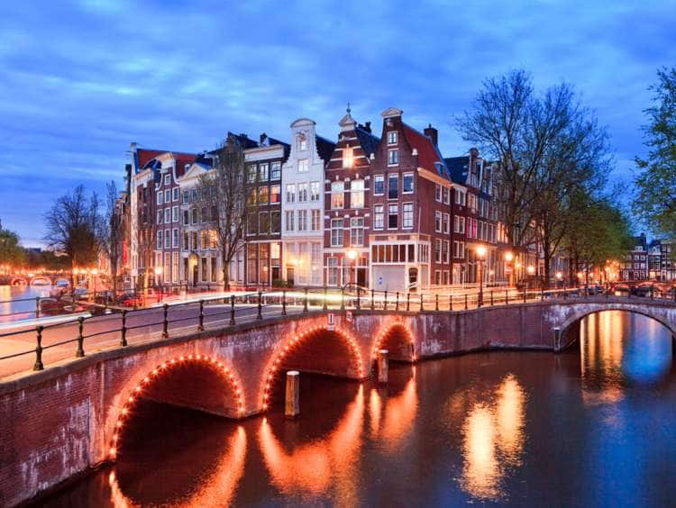Netherlands, North Holland, Benelux, Amsterdam, Typical Dutch houses and bridge on Keizersgracht and Leidesegracht Canals illuminated at dusk