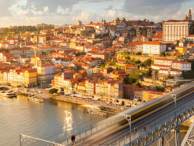 Portugal, Oporto, Douro, Porto at sunset with a train on Louis I bridge over Douro River