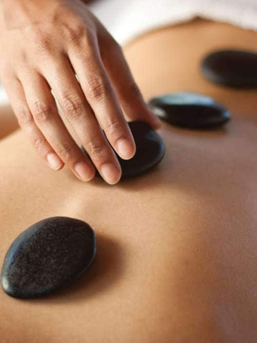 Hands massaging lower back with warm stones. You may also like: