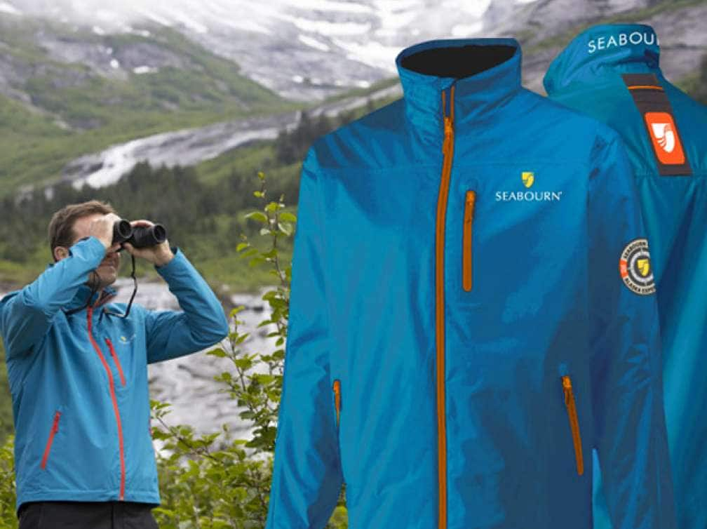 A man looking through a pair of Binoculars with Seabourn all-inclusive Alaska cruise jackets