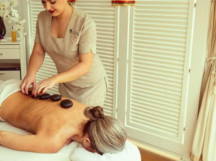 A woman relaxing with a hot stone massage from the spa on a small ship cruise