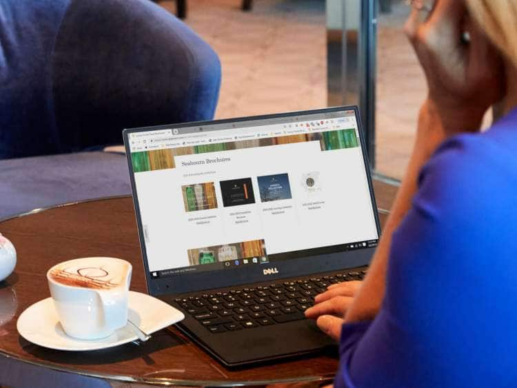 Woman on laptop selecting a Seabourn eBrochure to download while relaxing and drinking coffee in Seabourn Square on board an all-inclusive, ultra-luxury Seabourn ship
