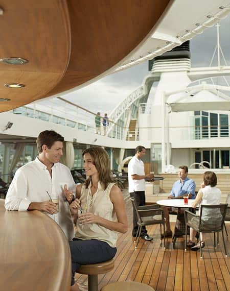 Happy couple seated at Patio bar on deck of Seabourn Quest