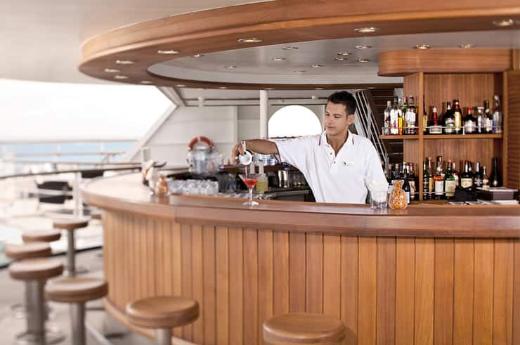 Bartender pouring tropical cocktails at beautiful hardwood ladened round bar.