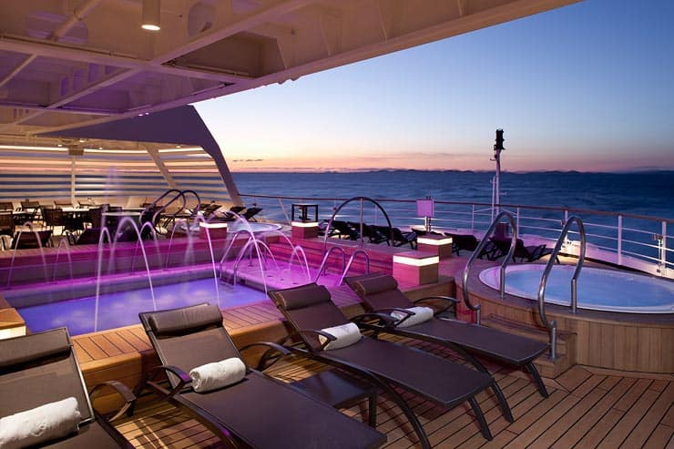 Outdoor whirlpools and with purple and pink lighting, water fountains cascading into the pools, deck chairs lined around them on deck with ocean in background.