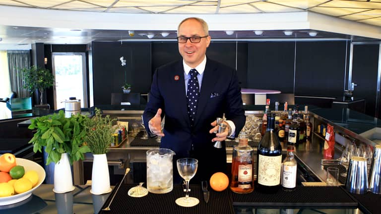 A photo of Mixologist Brian Van Flandern, a man with dark hair, smiling while making a cocktail he is wearing: horned rim glasses, a blue suit with a white shirt and blue tie with white polkadots. He is standing in a Seabourn Cruise Ship bar surrounded by bottles of spirits, glassware and pots of herbs.