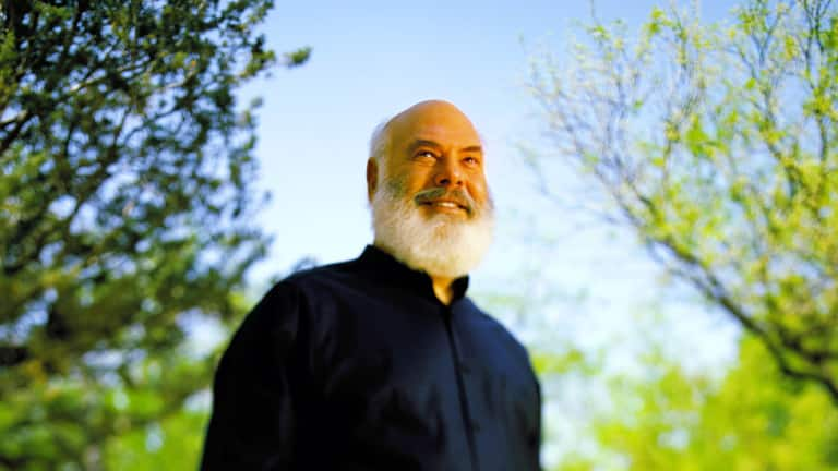 A photo of Doctor Andrew Weil wearing a black shirt, looking upward and smiling with large leafed trees backdropped by blue sky in the background.