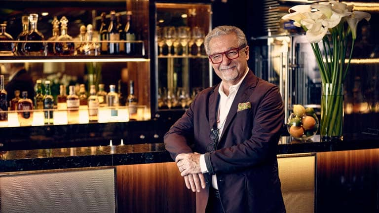 A photo of Adam D. Tihany: a man in a casual evening suit. He is smiling at a Seabourn bar; with his right arm resting on a black quartz bar counter, behind him a tall vase of calalillies and a glass bowl of: oranges, limes and lemons, amidst a sumptuous decor of: dark grained wood, mirrored glass behind premium spirits and recessed lighting.