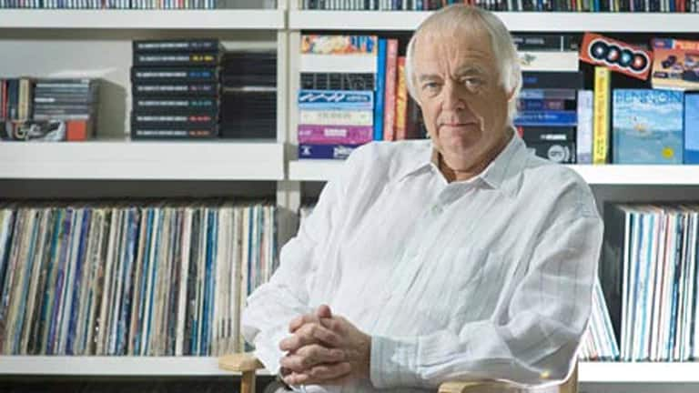 A photo of Sir Tim Rice wearing a white shirt with his hands folded, seated in a library.