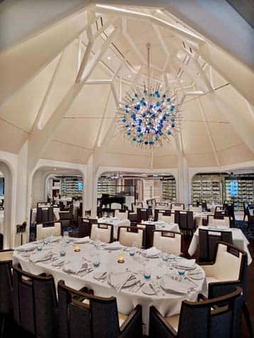 Seabourn Ovation Dining room - Formal dining room, walls draped in white silk, with a large modern crystal chandelere above oval tables, set in fine fashion with linen napkins folded gracefully adorning fine china and silverware.