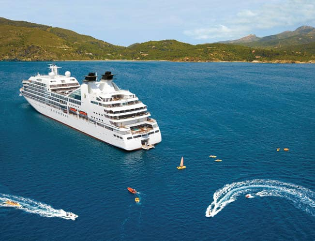 Cruise ship afloat in ocean with guests using kayaks, sailboats and rafts launching from floating marina attached to the ship's stern'.